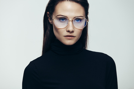 Close up portrait of woman wearing glasses staring with an intense expression. Female model in black dress on grey background.