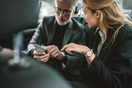 Young woman with senior businessman using mobile phone while traveling by a car. Business people using smart phone in taxi.