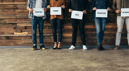 Laag gedeelte van zakenmensen die in een rij tegen een muur staan met de namen van hun respectievelijke afdelingen op een bordje. Kandidaten op de shortlist van een organisatie voor verschillende afdelingen.