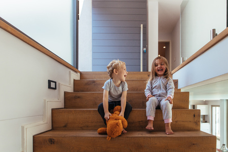 Joyful children sitting on stairway with a teddy bear. Laughing little boy and girl sitting on wooden stairs with teddy bear.
