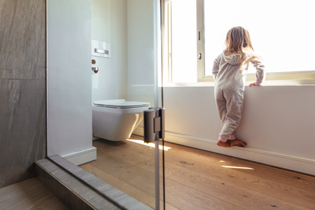 Little girl in bathroom standing by a big window and looking outside. Girl child inside a bathroom looking outside through a window.