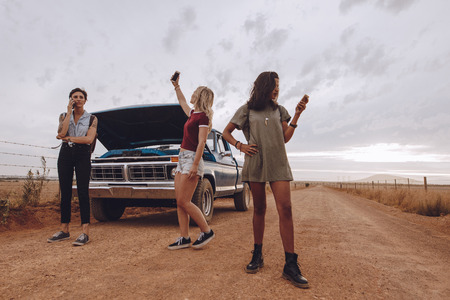 Female friends stranded in middle of a countryside road with problem in their car. Women using their phones to call road assistance.