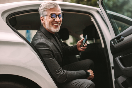 Portrait of smiling mature businessman sitting in the backseat of a cab. man taking a taxi for traveling. Banco de Imagens