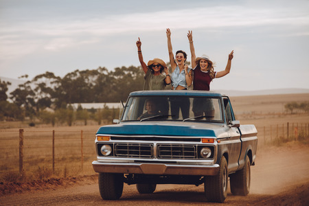 Three women on a roadtrip through countryside travel on the back of a pickup truck. Friends standing in the back of a open truck laughing with their hands raised.