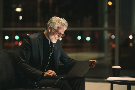 Smiling mature businessman working late on laptop in office lobby. Corporate professional looking at laptop and smiling. Banque d'images