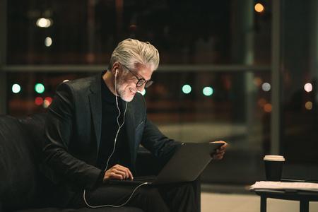 Sonriente hombre de negocios maduro trabajando hasta tarde en la computadora portátil en el vestíbulo de la oficina. Profesional corporativo mirando portátil y sonriendo.
