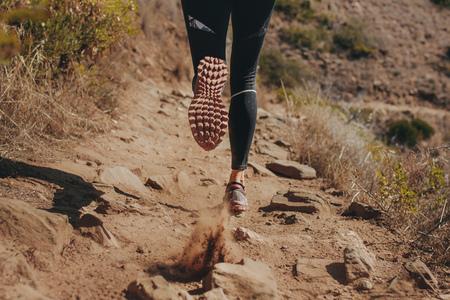 Woman runner legs running on mountain trail. Feet of woman runner running over stones on mountain trail. Imagens