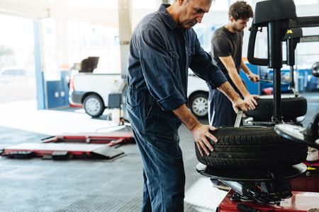 Mechanics working in car repair workshop. Auto repair workers working on tire replacing machine in auto repair shop. Stok Fotoğraf - 107322133
