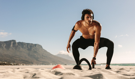 Man doing fitness workout at a beach using kettlebells. Bare chested athletic man lifting kettlebells wearing wireless headphones and mobile phone fixed to armband.