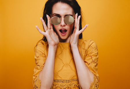 Portrait of beautiful female model wearing funky sunglasses. Attractive young woman in orange dress looking at camera with mouth open.