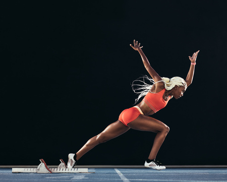 Side view of a female athlete starting her sprint on an all-weather running track on a black background. Runner using starting block to start her run on a running track.