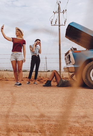 Woman making a selfie video to record the situation of broken down car, with friends trying to fix the problem. Stock Photo