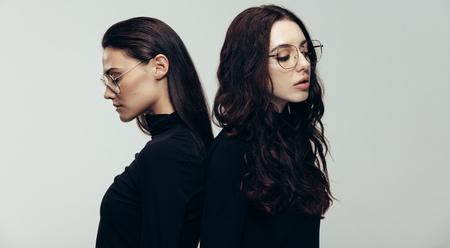 Two young woman in black outfit and glasses standing back to back. Two female models against grey background