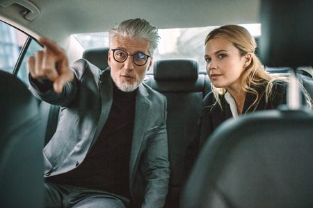 Two businesspeople traveling by car with man pointing away. Senior businessman showing something interesting to female while traveling by a taxi.
