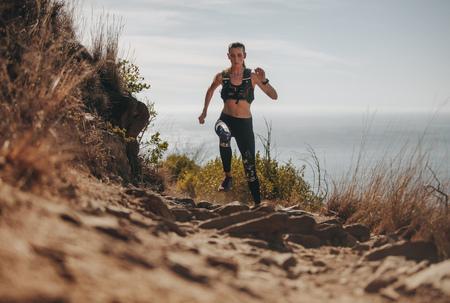 Fit Frau läuft den Bergpfad hinauf. Sportlerin, die Langlauf auf einer felsigen Spur übt.
