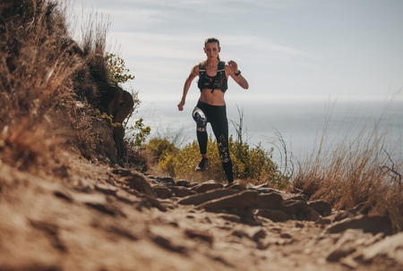 Fit woman running up the mountain trail. Female athlete practicing cross country running on a rocky trail.