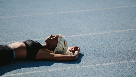 Woman athlete lying on the running track relaxing in the sun after workout. Female sprinter resting after workout lying on track on a sunny day.
