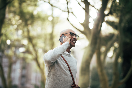 Man walking through park wearing office bag talking on mobile phone. Smiling businessman talking over cell phone while walking on city street to work. Stock Photo