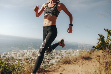 Sportswoman sprinting over rocky trail. Female running downhill on mountain path.