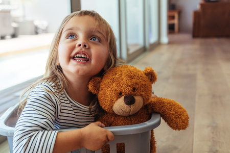 Adorable young girl sitting in a washing basket with her teddy bear. Beautiful girl child playing in a washing basket at home. 스톡 콘텐츠