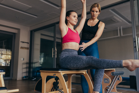 Fitness women doing pilates workout sitting in a gym guided by her trainer. Trainer guiding a woman doing pilates workout at the gym.