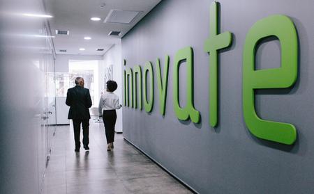 Rear view of two business people walking through office corridor. Business colleagues walking in office hallway. Foto de archivo
