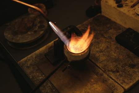 Melting gold in a small crucible for making jewelry. Goldsmith using torch flame to heat and melt the silver granules in a crucible. Foto de archivo - 107296581