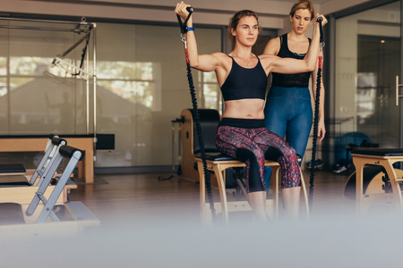 Woman sitting on a pilates training machine pulling stretch bands. Woman doing pilates workout at the gym while her trainer looks on. Фото со стока - 107296591