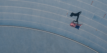 Aerial view of an athlete running on athletic track holding the american flag over the head. Top view of a sprinter celebrating victory on track running holding the US flag with shadow falling on the side. Stock Photo