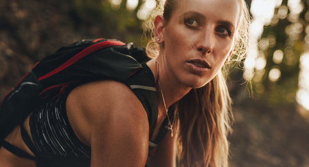 Close up portrait of fit woman in sportwear wearing hydration pack sitting outdoors and looking away. Mountain trail runner resting after a run.