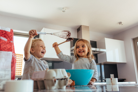 Cute little boy and girl fighting with whisk and spatula while mixing batter in a bowl. Siblings enjoying baking in home kitchen. 스톡 콘텐츠
