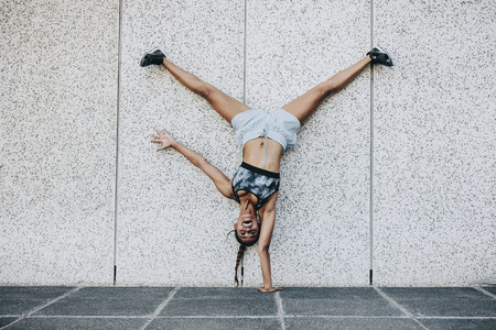 Female athlete in training clothes doing an acrobatic move turning upside down outdoors. Acrobatic fitness woman balancing upside down on one hand with legs in air. Stockfoto
