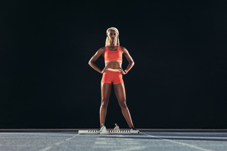 Female sprinter standing beside a starting block on running track on a black background. Female runner standing at the start line on an all-weather running track with hands on hip. Stock Photo