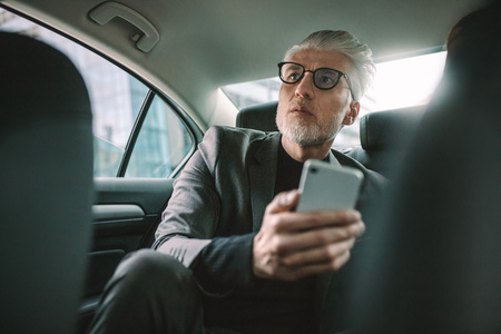 Senior businessman sitting on backseat of taxi with mobile phone. Mature male commuter traveling by a cab. Stock Photo