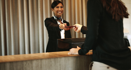 Smiling female concierge returning the documents to hotel guest after check-in process. Female client receiving her documents at hotel reception desk after check-in. 版權商用圖片