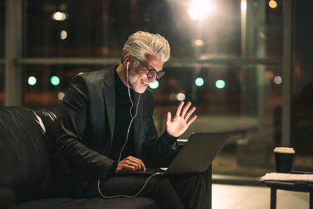 Middle aged man on video call using a laptop in office lobby. Smiling businessman late at night in office making gestures on a video call.
