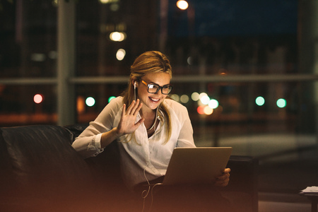 Woman on video call using a digital tablet sitting in office lobby. Smiling businesswoman late at night in office making gestures on a video call. Stock Photo
