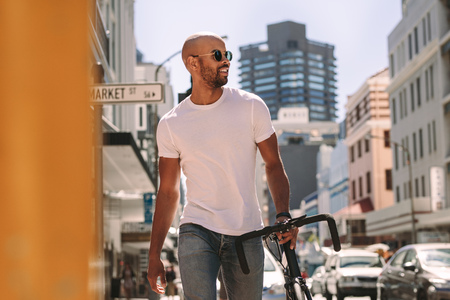 Handsome young man in casuals walking down the street with a bicycle. African man in casuals walking outdoors in the city with a bike. Stok Fotoğraf