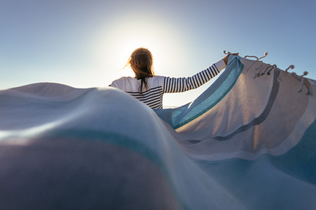 Rear view of a woman standing while holding a flying cloth in both hands. Woman holding a drape with sun flare in the background.