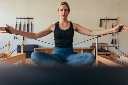 Woman sitting on a pilates training machine pulling stretch bands with both hands at the gym. Woman sitting on a pilates training equipment with crossed legs and doing workout. Stockfoto