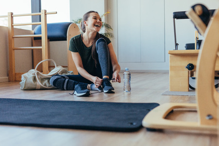 Smiling woman wearing her shoes after workout sitting at the gym. Woman sitting on floor at a pilates gym with her gym bag tying her shoelaces.