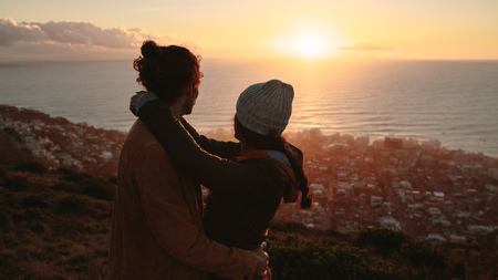 Romantic couple together admiring the sunset over sea from on mountain. Young man and woman together on mountain peak with seascape in background.