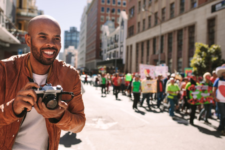 Smiling african photographer takes pictures of activists on road. Man taking photographs of people walking in a rally on city street.