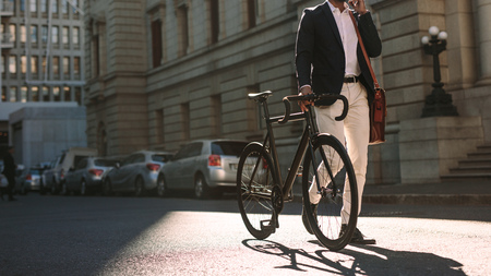 Cropped image of businessman walking on city street with a bicycle and talking on mobile phone. Man in formal wear going to work with cycle using phone.