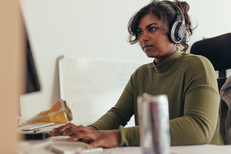 Female programmer working in a software developing company office. Woman wearing headphones coding on desktop computer.