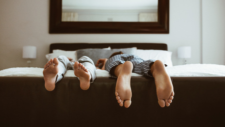 Feet of two people sleeping on bed. People sleeping on bed in different positions.