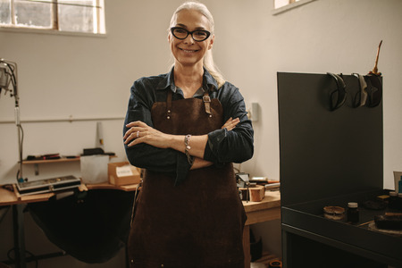 Portrait of confident senior female jeweler standing in her workshop. Woman goldsmith wearing apron and eyeglasses standing with her arms crossed and looking at camera smiling in jewelry making shop. Stock Photo