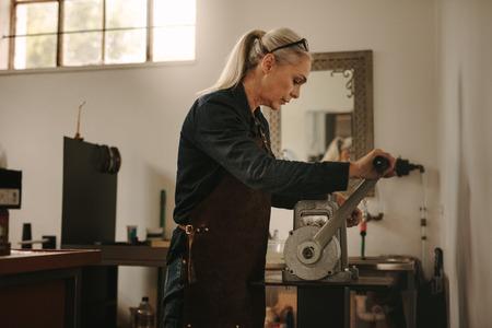 Femme mûre orfèvre artisanat métal sur machine à rouler artisanale. Femme âgée utilisant une machine à rouler les métaux traditionnels dans un atelier de bijoux.