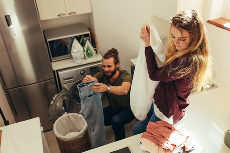 Happy couple folding their clothes and arranging them after wash. Couple doing their laundry work together at home.