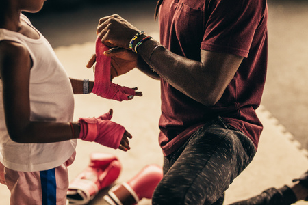 Boxing coach wrapping bandage on hands and knuckles of a kid before putting on boxing gloves.